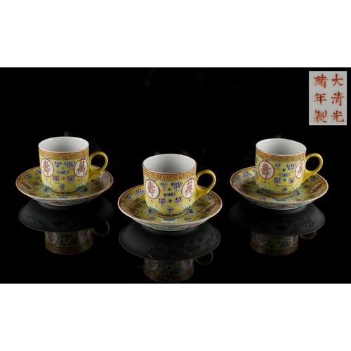 269 - A set of three Chinese famille rose yellow ground 'Birthday' cups & saucers, iron red Guangxu 6-char...