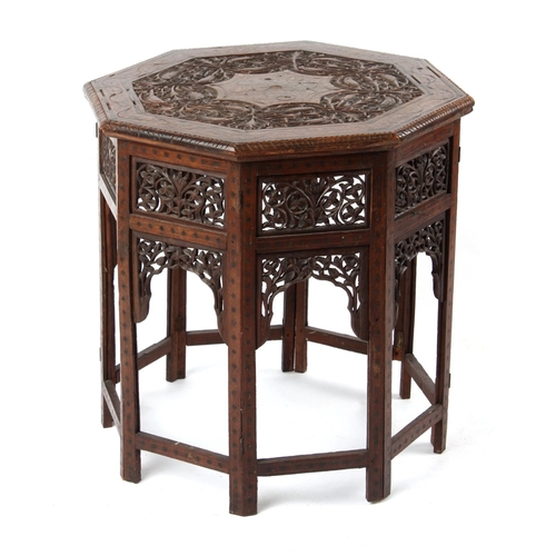 44 - Property of a gentleman - an Indian carved teak & brass inlaid octagonal folding table, 23ins. (58.5...