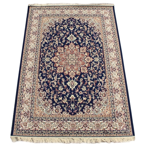 90 - A Kashan style rug with blue ground, 79 by 55ins. (200 by 140cms.) (see illustration)....