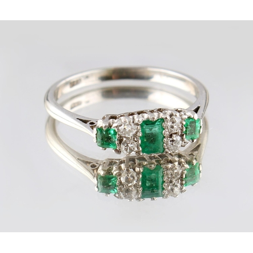 35 - An unmarked white gold emerald & diamond ring, set with a rectangular cut emerald & two square cut e...