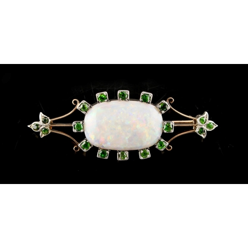 27 - An opal & demantoid garnet brooch, the oval opal measuring approximately 23 by 15mm, approximately 9...