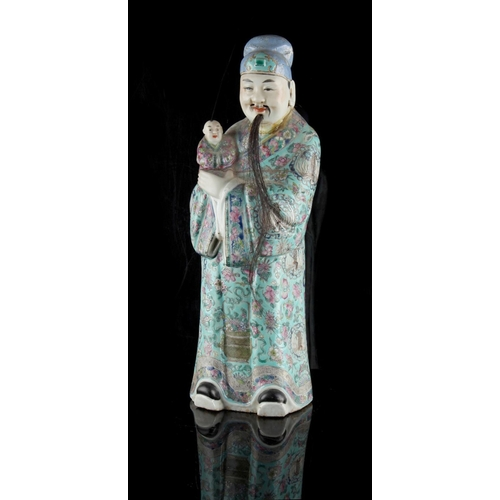 48 - Property of a gentleman - a late 19th century Chinese famille rose figure of a mandarin holding a bo...