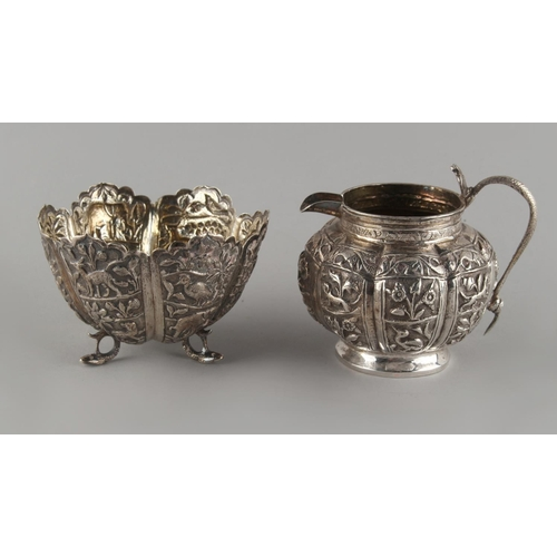 11 - Property of a lady of title - a late 19th / early 20th century Indian white metal cream jug and matc...