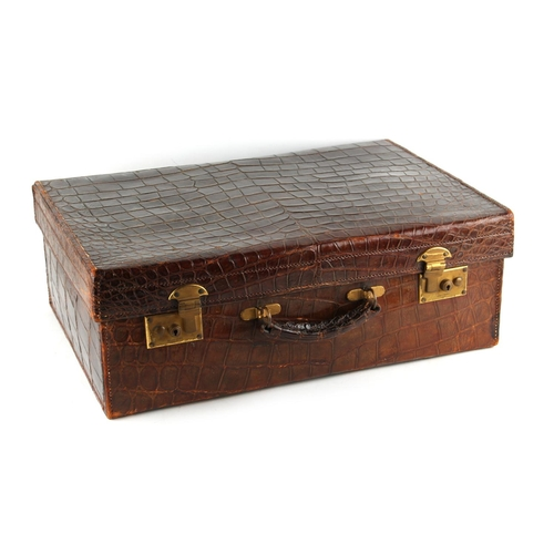 34 - Property of a deceased estate - an early 20th century crocodile skin suitcase, with brass double lev...