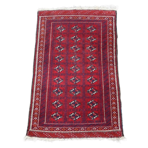 45 - Property of a deceased estate - an Afghan rug with three rows of guls on a red ground, 57 by 35ins. ...