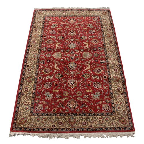 54 - Property of a gentleman - a Tabriz style woollen hand knotted carpet, decorated with various animals...