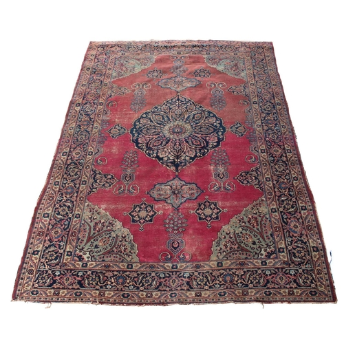 58 - Property of a gentleman - an antique Kirman Laver carpet, worn, 132 by 92ins. (336 by 234cms.)....