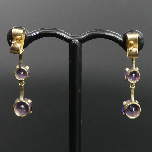 19 - A pair of 9ct gold 3 graduated amethyst drop earrings. 1.4 grams. 23mm long. Bottom stones are 5mm i...