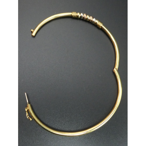 38 - 9 carat gold hinged bangle with 3 colour gold rings embellishment. 5.3 grams. 2.7mm and 4.3 mm wide....