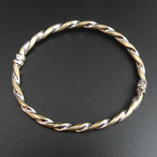58 - 9ct white and yellow gold twisted design hinged bangle. 4.9 grams. 4.2mm wide. UK Postage £10.