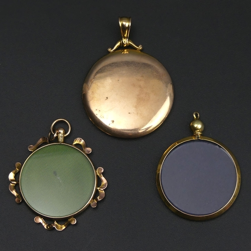 32 - Two 9 carat gold picture locket pendants and one yellow metal example. 30 mm, 33 mm and 35 mm in dia...