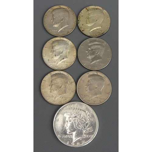 55 - 1925 silver dollar and six Kennedy half dollars. UK Postage £12.