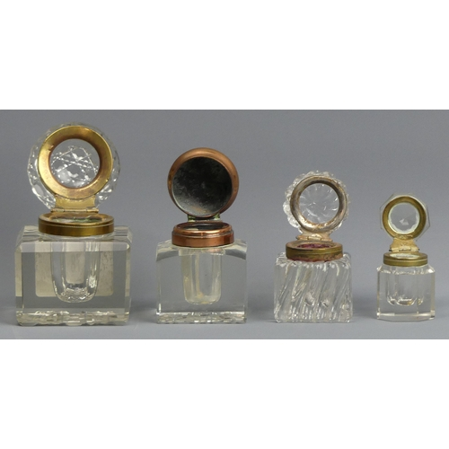 78 - Four late 19th century glass inkwells with hinged covers. Tallest 7.5 cm.  UK Postage £15.