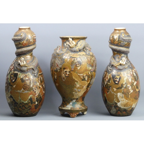 91 - A garniture of three Japanese Meiji period Satsuma pottery vases, signatures to the bases and in the...
