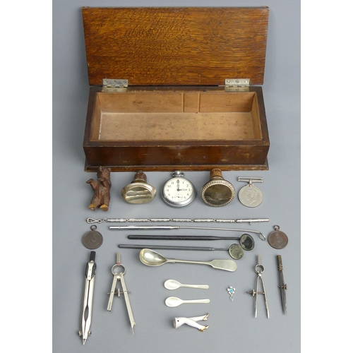 97 - An old oak box and contents, including a Black Forest bear, Geometry tools, medals and other collect...