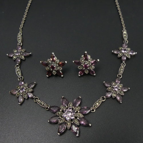 115 - Sterling silver amethyst and marcasite flower design necklace and earrings. 15.8 grams. 43.5 cm long...