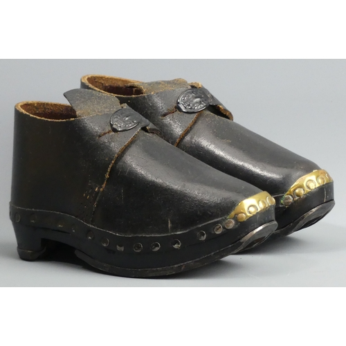 203 - A vintage pair of child's wood, leather, steel and brass clogs. 17 cm long.