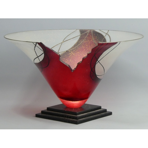 267 - A ruby and frosted studio art glass bowl of broken design on a black crackle glass base. 35 cm in di...