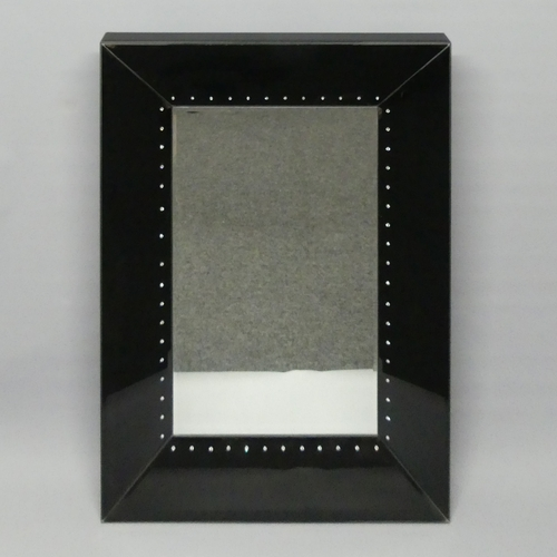 276 - Black glass framed bevelled mirror with crystal decoration. 102 cm x 67 cm.