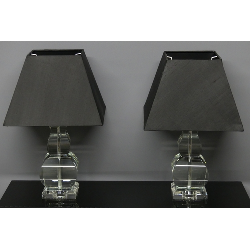280 - A pair of heavy glass table lamps with black shades. 46 cm high.
