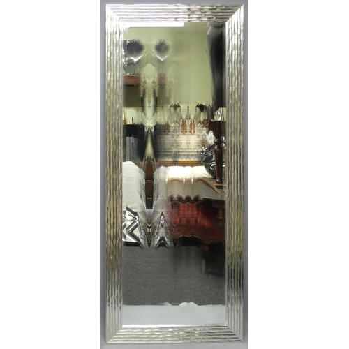 291 - A large bevelled glass wall mirror in a wave design silvered frame. 79 x 186 cm.