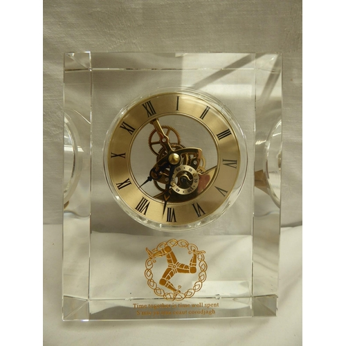 37 - Quartz clock held in a glass case with Manx Three Legs emblem to front - 15.5 x 12cm