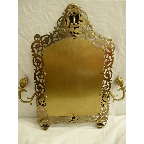 7 - A cast gilt metal wall mirror with swinging candlestick arms in the Rococo style with Bacchus to top...
