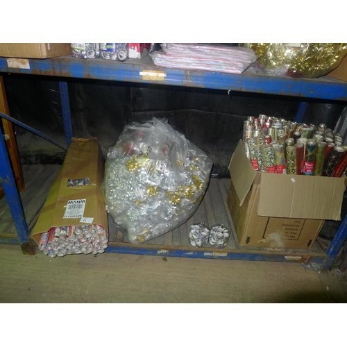 11 - A quantity of various Christmas related items wrapping paper, ribbon etc. Contents of one shelf...