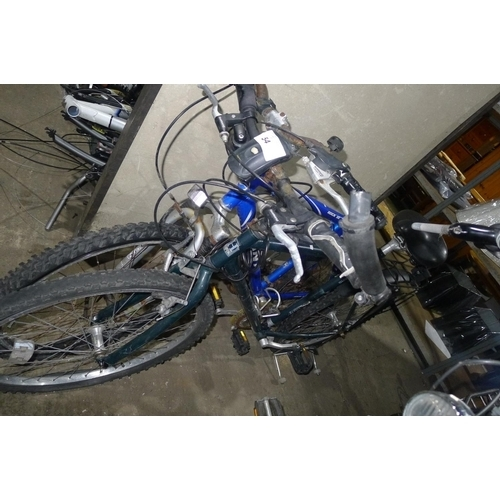 54 - Two adult mountain bikes in need of repair: one Giant Rock SE and one Hawk...