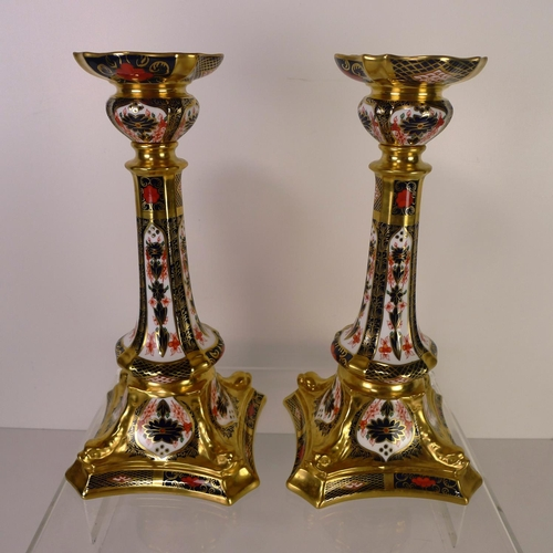 404 - A pair of of Royal Crown Derby old Imari 1128 dolphin based candlesticks, 27cm tall, with boxes