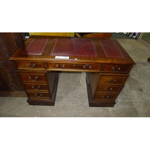 1385 - A reproduction mahogany rectangular topped pedestal desk with a tooled leather surface, 1 central an...