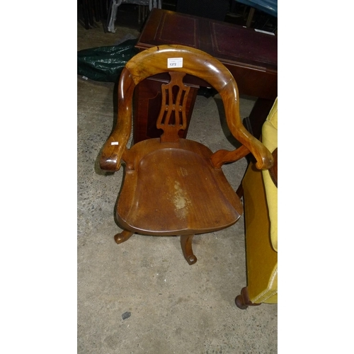1372 - An Edwardian mahogany swivel office elbow chair with a shaped wooden seat...