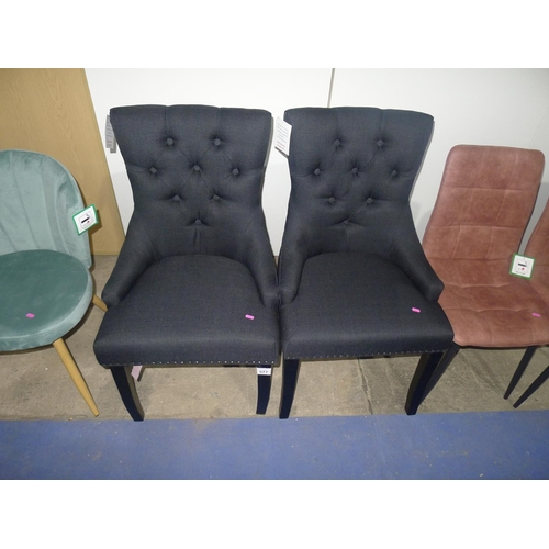 577 - A pair of black upholstered button back dining chairs with black frames and ring handles in middle o...