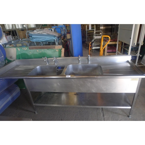 3004 - A large commercial stainless steel twin deep sink unit with draining board on both sides and shelf b...