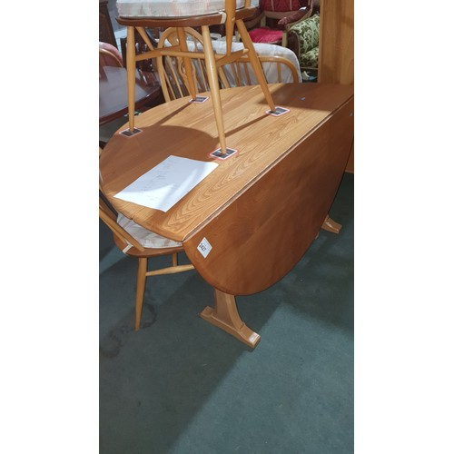 2427 - A vintage Ercol blonde wood circular top drop leaf dining table and a set of 6 matching high back, r...