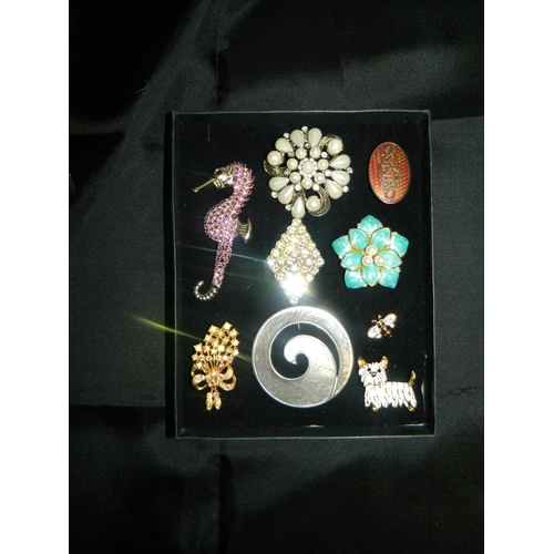 198 - Box with 9 costume jewelery brooches including a seahorse...