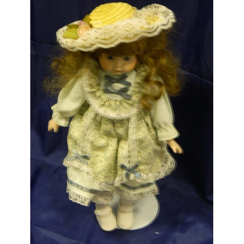 355 - Doll dressed in print dress and hat...