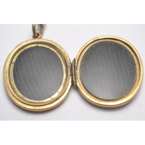 19 - Victorian oval yellow metal mourning locket on chain engraved profusely and decorated with blue enam...
