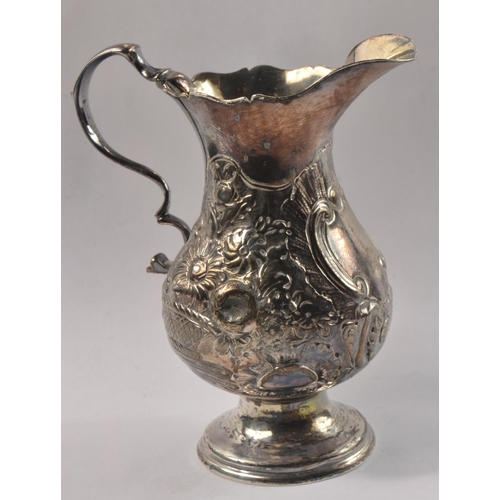 19D - An antique LONDON Hallmarked 1838( to base) small beautiful repousse decorated jug (maximum width 9c...