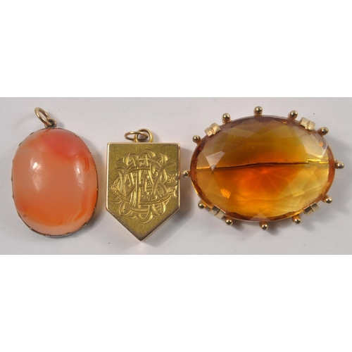 1T - A VINTAGE collection of jewellery to include a large yellow metal ladies brooch with an amber style ...