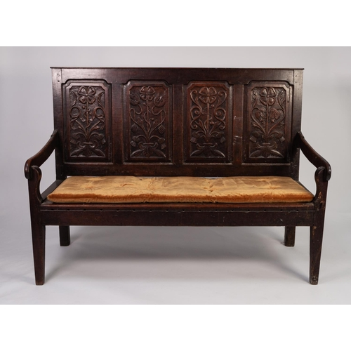 47 - LATE EIGHTEENTH CENTURY CARVED OAK SETTLE, of typical form, the four panelled back well carved with ...