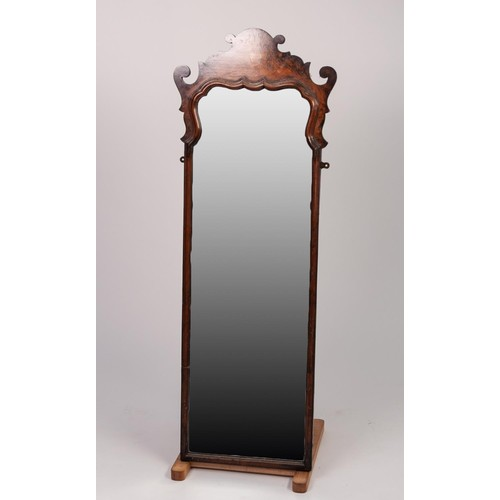 43 - GEORGE I STYLE FIGURED WALNUT ROBING MIRROR, the oblong, bevel edged plate with shaped top, housed i...