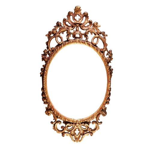 46 - TWENTIETH CENTURY CARVED GILT WOOD WALL MIRROR, the later oval plate housed in a gadroon moulded fra...