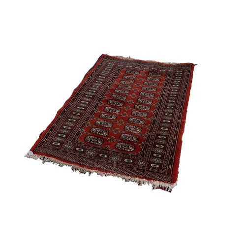 3 - BOKHARA PATTERN EASTERN RUG, with two rows of primary guls on a crimson field, with principal border...