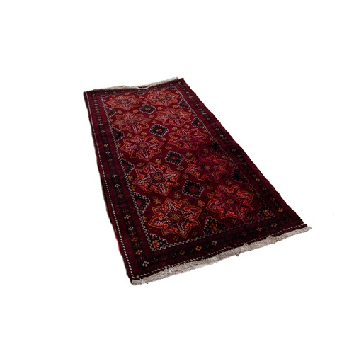 6 - SHIRAZ PERSIAN RUG, with two rows of five stellate medallions, stencilled on the dark crimson field ...
