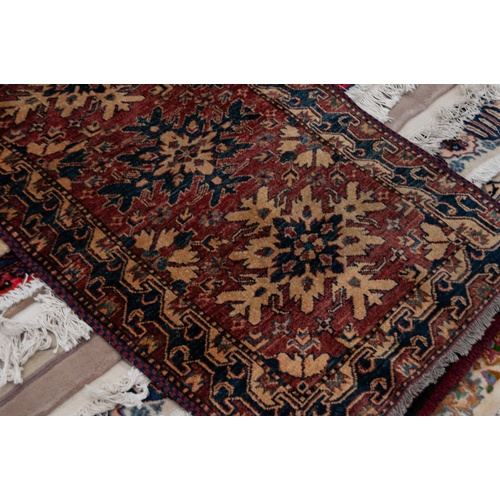 20 - SHIRAZ PERSIAN RUNNER with eight splash pattern medallions in blue and fawn on a wine red and floral...