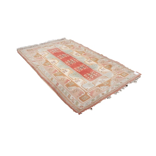 23 - TURKISH LARGE ALL-WOOL EMBOSSED RUG, with a narrow salmon pink central panel with five square repeat...