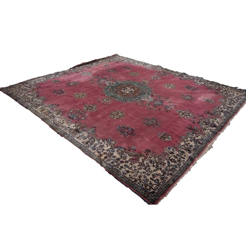 40 - LARGE, POSSIBLY EUROPEAN, PERSIAN STYLE CARPET, having a rose pink field, large green, brown and whi...
