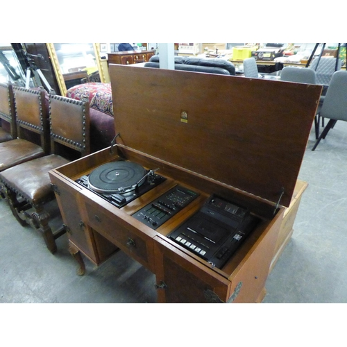 213 - A DYNATRON WALNUT AND MAHOGANY CROSSBANDED RADIOGRAM, IN THE FORM OF A PEDESTAL DESK WITH GREEN LEAT...