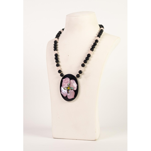 55 - CHINESE SINGLE STRAND NECKLACE of black beads and eight white jade beads, with gold plated torpedo c...